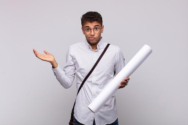 困惑して混乱していると感じている若い建築家の男、疑わしい、重みを付けたり、面白い表現でさまざまなオプションを選択したりする