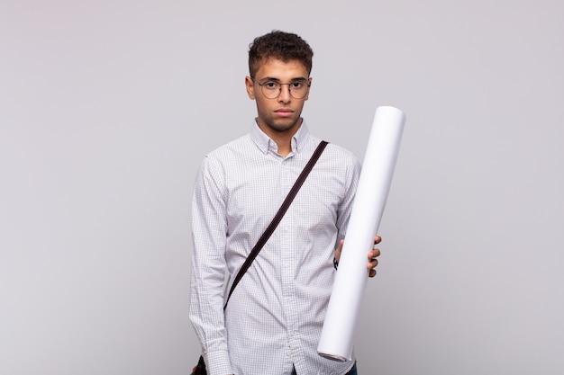 Молодой архитектор чувствует себя грустным, расстроенным или злым и смотрит в сторону с отрицательным отношением, хмурясь в знак несогласия