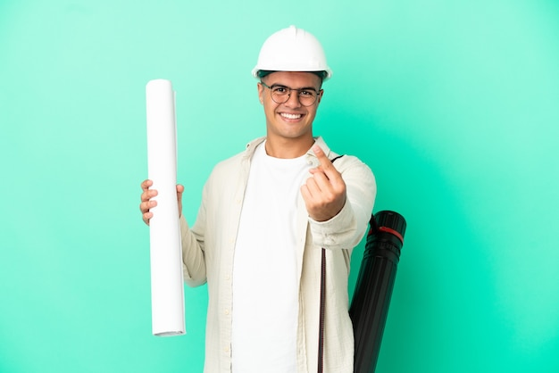 Young architect man holding blueprints over isolated background doing coming gesture