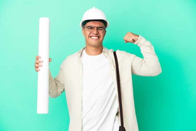 Young architect man holding blueprints over isolated background doing strong gesture