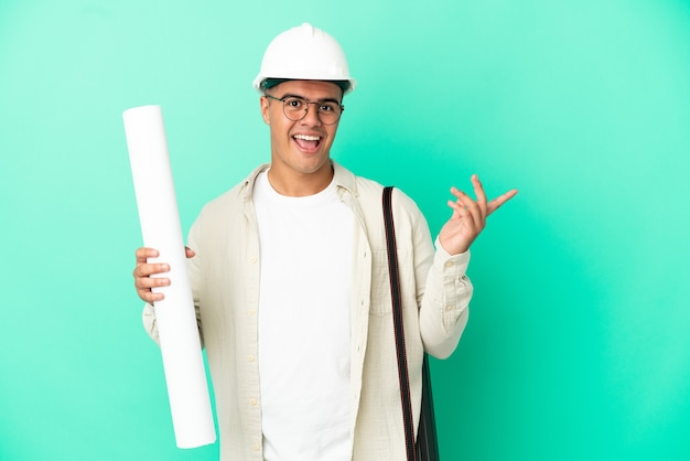 Young architect man holding blueprints over isolated background extending hands to the side for inviting to come
