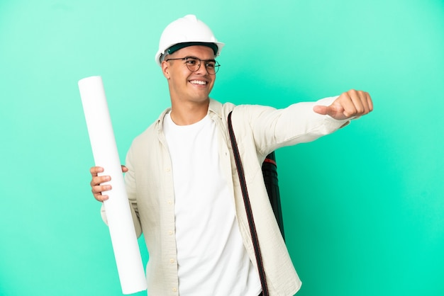 Young architect man holding blueprints over isolated background giving a thumbs up gesture