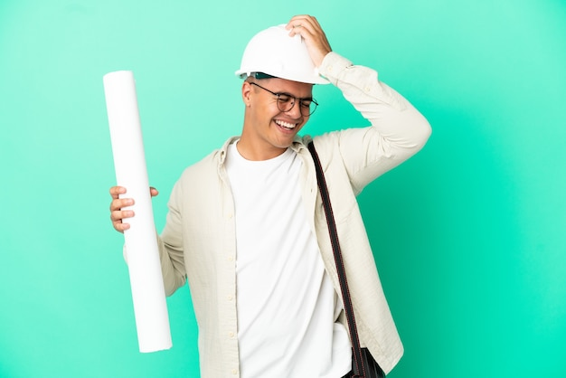 Young architect man holding blueprints over isolated background has realized something and intending the solution