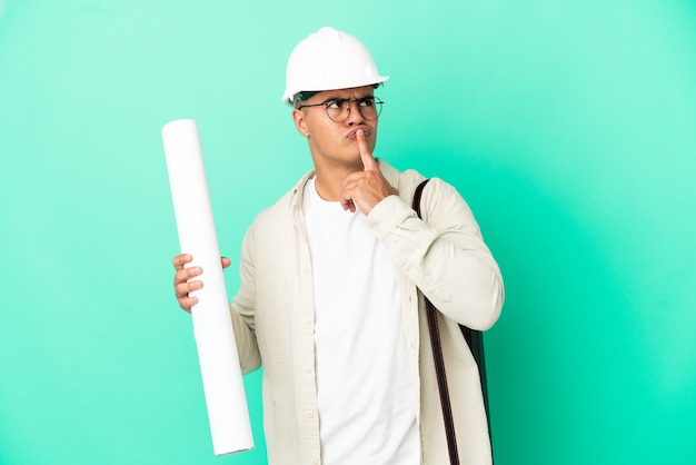 Young architect man holding blueprints over isolated background having doubts while looking up