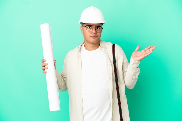 Young architect man holding blueprints over isolated background having doubts while raising hands