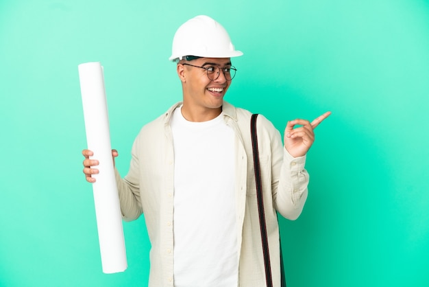 Young architect man holding blueprints over isolated background intending to realizes the solution while lifting a finger up
