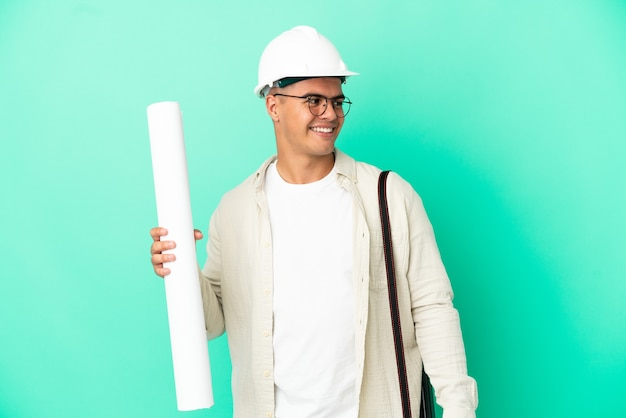 Young architect man holding blueprints over isolated background looking to the side and smiling