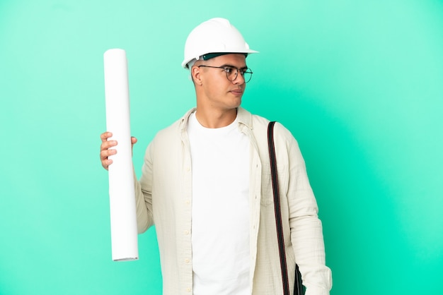 Young architect man holding blueprints over isolated background looking to the side