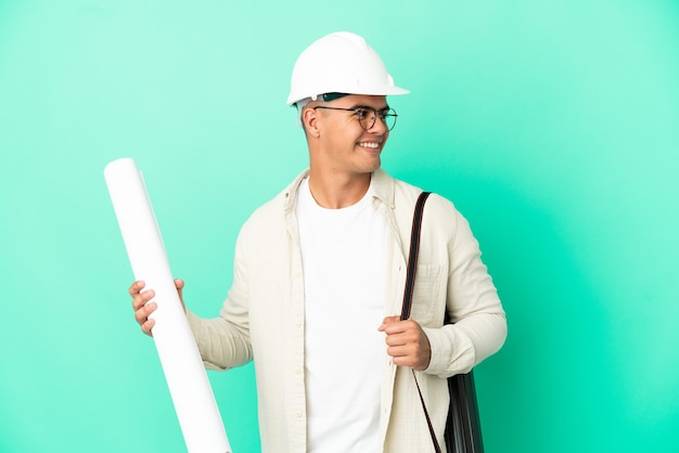 Young architect man holding blueprints over isolated background looking side