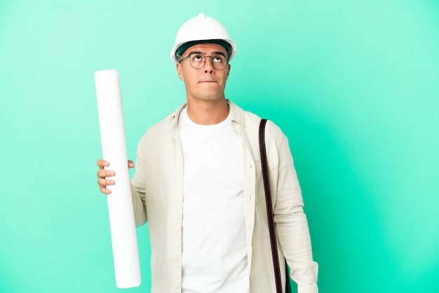 Young architect man holding blueprints over isolated background and looking up