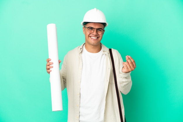 Young architect man holding blueprints over isolated background making money gesture