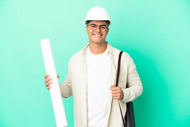 Young architect man holding blueprints over isolated background posing with arms at hip and smiling