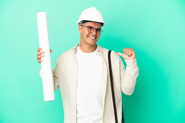 Young architect man holding blueprints over isolated background proud and self-satisfied