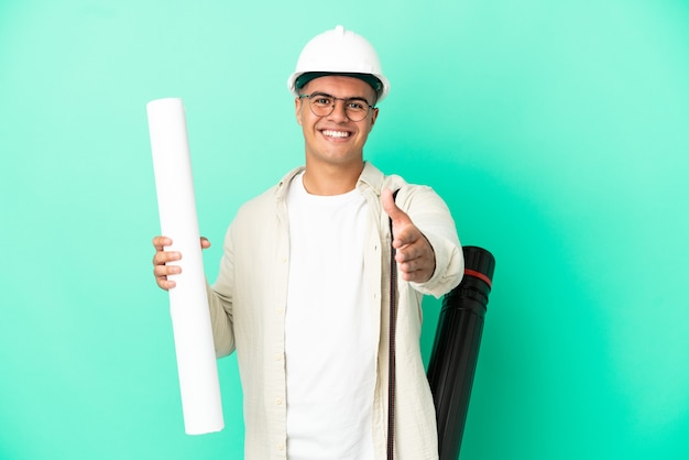 Young architect man holding blueprints over isolated background shaking hands for closing a good deal