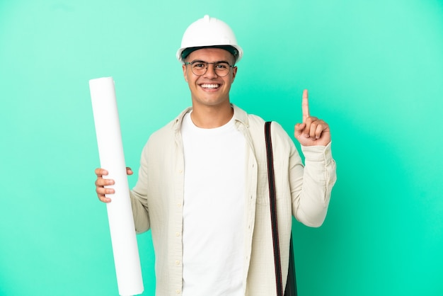 Young architect man holding blueprints over isolated background showing and lifting a finger in sign of the best