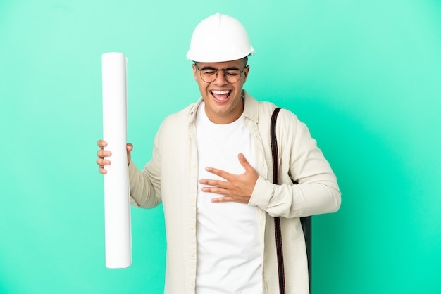 Young architect man holding blueprints over isolated background smiling a lot
