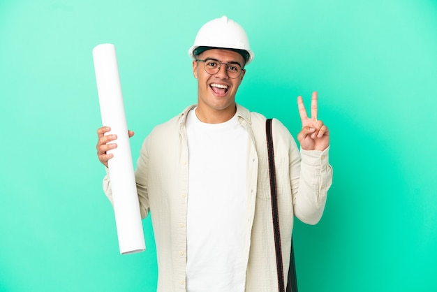 Young architect man holding blueprints over isolated background smiling and showing victory sign