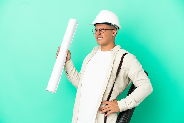 Young architect man holding blueprints over isolated background suffering from backache for having made an effort