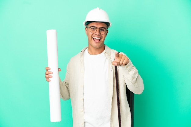 Young architect man holding blueprints over isolated background surprised and pointing front