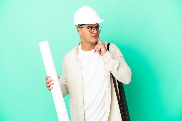 Young architect man holding blueprints over isolated background thinking an idea while looking up