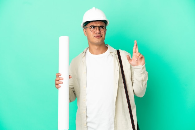 Young architect man holding blueprints over isolated background with fingers crossing and wishing the best