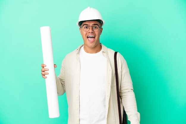 Young architect man holding blueprints over isolated background with surprise facial expression