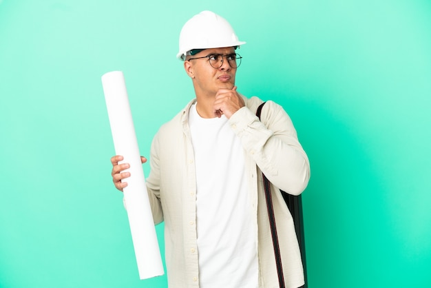 Young architect man holding blueprints over isolated wall having doubts