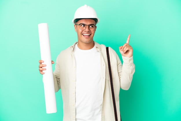 Young architect man holding blueprints over isolated wall pointing up a great idea