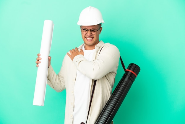 Young architect man holding blueprints over isolated wall suffering from pain in shoulder for having made an effort