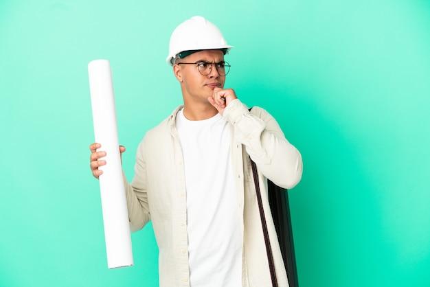 Молодой архитектор мужчина держит чертежи на изолированном фоне и смотрит вверх