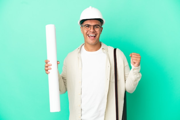 우승자 위치에서 승리를 축하하는 고립 된 배경 위에 청사진을 들고 젊은 건축가 남자