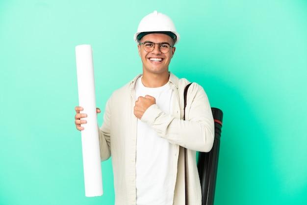 승리를 축하하는 격리 된 배경 위에 청사진을 들고 젊은 건축가 남자