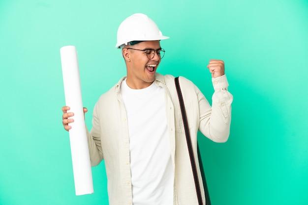 Молодой архитектор мужчина держит чертежи на изолированном фоне празднует победу