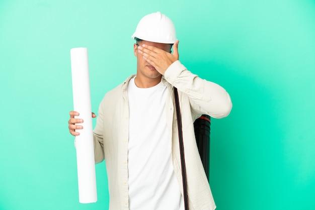 Молодой архитектор мужчина держит чертежи на изолированном фоне, закрывая глаза руками. не хочу что-то видеть
