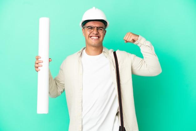 Молодой архитектор мужчина держит чертежи на изолированном фоне, делая сильный жест
