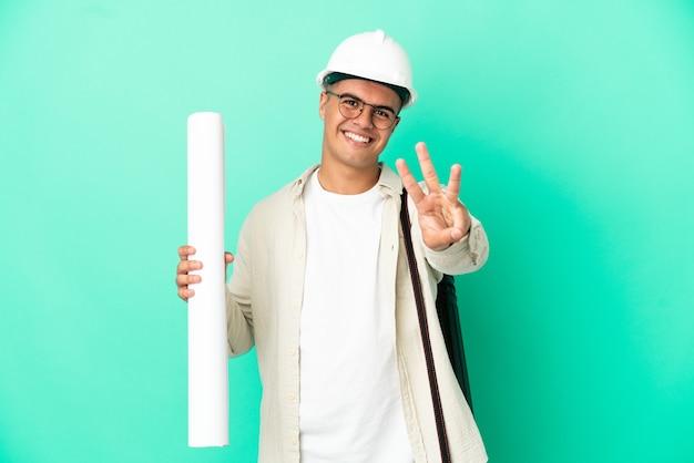 외진 배경 위에 청사진을 들고 행복하고 손가락으로 세 개를 세는 젊은 건축가