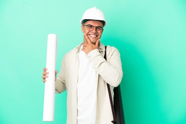 Молодой архитектор мужчина держит чертежи на изолированном фоне счастливым и улыбается