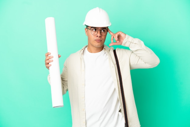 Молодой архитектор мужчина держит чертежи на изолированном фоне, сомневаясь и думая