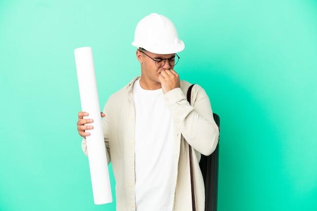 의심을 갖는 고립 된 배경 위에 청사진을 들고 젊은 건축가 남자