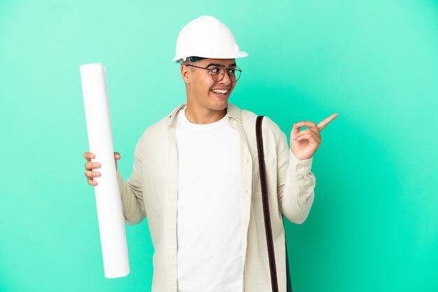 격리된 배경 위에 청사진을 들고 있는 젊은 건축가 남자는 손가락을 들어올리면서 솔루션을 실현하려고 합니다.