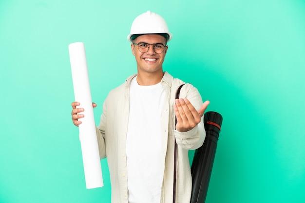 Молодой архитектор мужчина держит чертежи на изолированном фоне, приглашая прийти с рукой. счастлив что ты пришел
