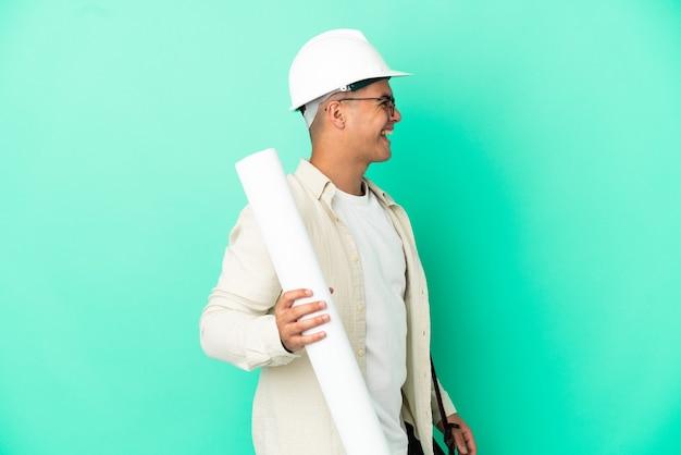Молодой архитектор мужчина держит чертежи на изолированном фоне, смеясь в боковом положении