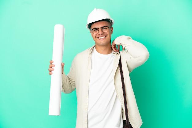 Молодой архитектор мужчина держит чертежи на изолированном фоне смеясь
