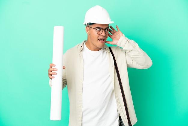 귀에 손을 넣어 뭔가를 듣고 격리 된 배경 위에 청사진을 들고 젊은 건축가 남자