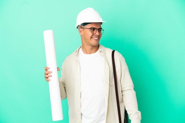 외진 배경 위에 청사진을 들고 옆을 바라보며 웃고 있는 젊은 건축가