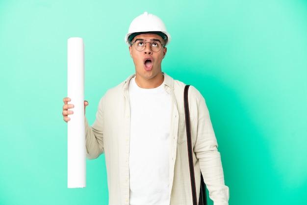 Молодой архитектор мужчина держит чертежи на изолированном фоне, глядя вверх и с удивленным выражением лица