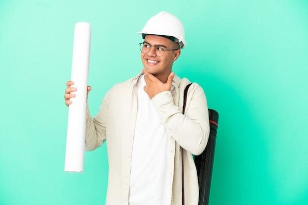 웃는 동안 찾고 격리 된 배경 위에 청사진을 들고 젊은 건축가 남자
