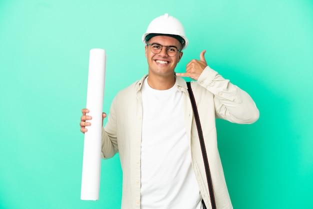 Молодой архитектор человек, держащий чертежи на изолированном фоне, делая телефонный жест. перезвони мне знак