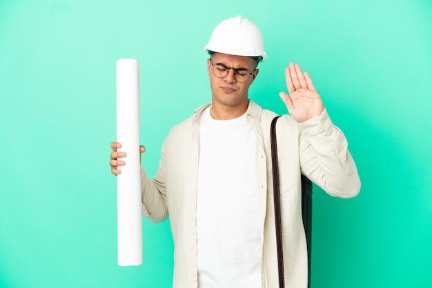 젊은 건축가 남자 중지 제스처를 만드는 격리 된 배경 위에 청사진을 들고 실망