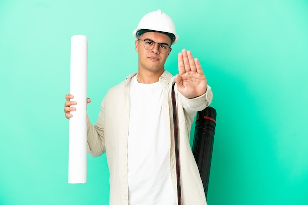 Молодой архитектор мужчина держит чертежи на изолированном фоне, делая стоп-жест
